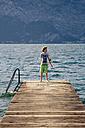 Italy, Veneto, Brenzone, Magugnano di Brenzone, Wooden boardwalk and boy - LVF001820