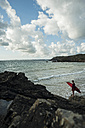 France, Brittany, Camaret-sur-Mer, teenage boy with surfboard at the ocean - UUF001656