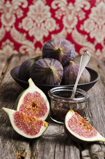 Sliced and whole figs and glass of fig jam on wooden table - ODF000826