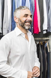 Portrait of smiling businessman buttoning his shirt at his walk-in closet - MBEF001198