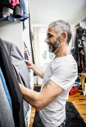 Man choosing clothes at his walk-in closet - MBEF001199