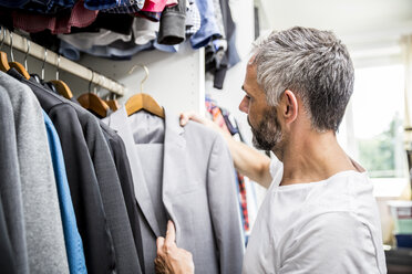 Man choosing clothes at his walk-in closet - MBEF001200