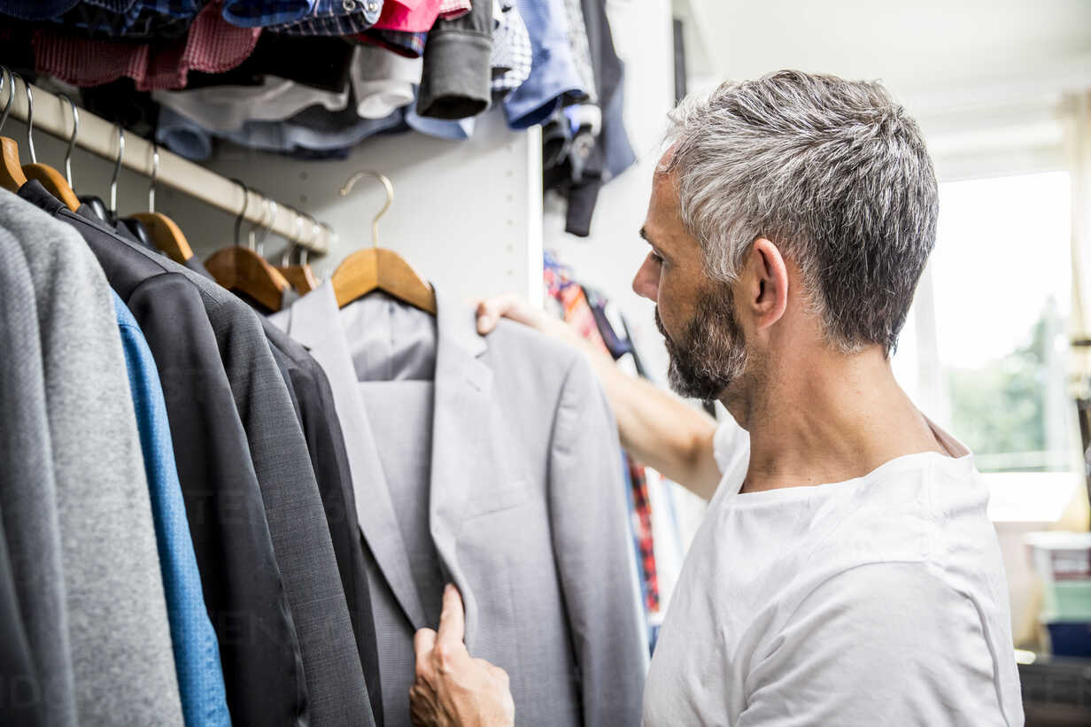 Man choosing clothes at his walk-in closet - MBEF001200 - Martin Benik/Westend61