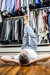 Man with hands behind his head and feet up in the air lying on the floor of his walk-in closet - MBEF001201