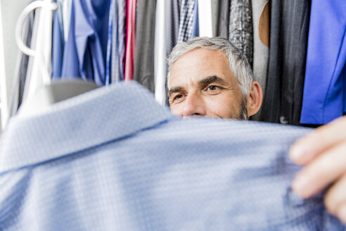 Man choosing jacket at his walk-in closet - MBEF001212