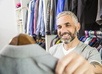 Portrait of smiling man choosing jacket at his walk-in closet - MBEF001213
