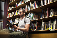 Student using digital tablet in a library - ZEF000832