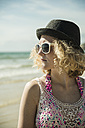 Portrait of teenage girl standing at waterside of the beach wearing hat and sunglasses - UUF001676