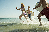 Three teenagers with surfboards running at waterside of the sea - UUF001685
