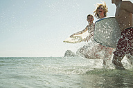 Three teenagers with surfboards running at waterside of the sea - UUF001687