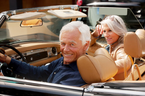 Portrait of a smiling senior couple sitting in a convertible car - CHAF000170