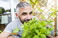Portrait of smiling man gardening on his balcony - MBEF001107