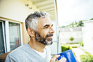 Portrait of smiling man relaxing with cup of coffee on his balcony - MBEF001116