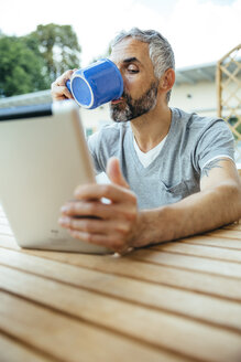 Portrait of man sitting on his balcony drinking coffee using digital tablet - MBEF001120