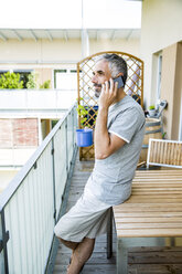 Man on his balcony telephoning with smartphone - MBEF001148