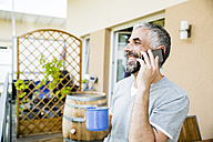 Man on his balcony telephoning with smartphone  holding cup of coffee - MBEF001231