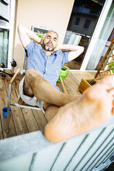 Man relaxing on his balcony - MBEF001127