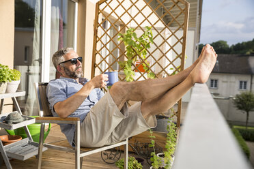 Man wearing sunglasses relaxing on his balcony with a cup of coffee - MBEF001129