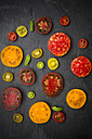 Slices of different heirloom tomatoes on slate - LVF001861