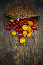 Basket of different organic heirloom tomatoes on wooden table - LVF001870