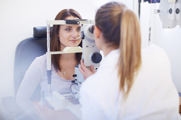Eye doctor examining woman's vision - ZEF000612