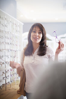 Woman at the optician trying on glasses - ZEF000613