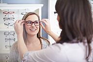 Woman at the optician trying on glasses - ZEF000638