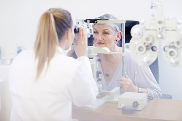 Eye doctor examining senior woman's vision - ZEF000650