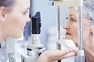 Eye doctor examining senior woman's vision - ZEF000652
