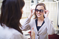 Woman at the optician trying on sunglasses - ZEF000660