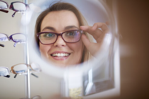 Woman at the optician trying on glasses - ZEF000700