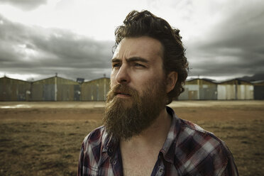 Serious man with full beard in abandoned landscape - KOF000018