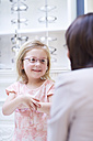 Girl at the optician trying on glasses - ZEF000592