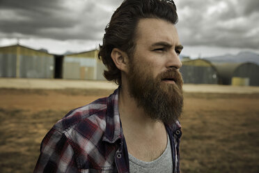 Serious man with full beard in abandoned landscape - KOF000040