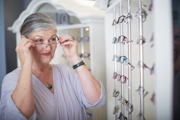 Senior woman at the optician trying on glasses - ZEF000744