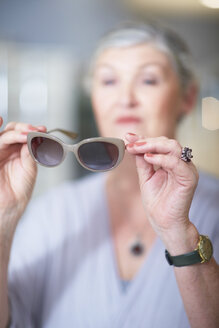 Senior woman at the optician trying on sunglasses - ZEF000632