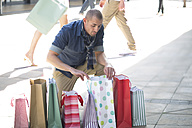 Man looking into shopping bag - ZEF000158