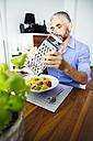 Man grating parmesan on his pasta - MBEF001134