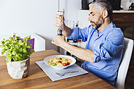 Man flavouring his pasta with pepper - MBEF001136