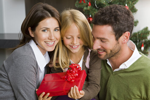 Happy couple and her daughter with Christmas present at home - CHAF000190
