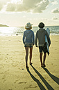 Teenage couple walking on the beach at evening twilight - UUF001698