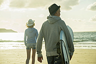Teenage couple walking on the beach at evening twilight - UUF001752
