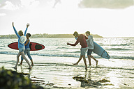 Woman and three teenagers with surfboards running at waterside of the sea - UUF001753