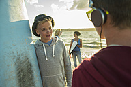 Two teenage boys communicationg on the beach - UUF001711