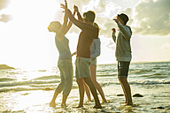 Woman and three teenagers having fun on the beach by sunset - UUF001715