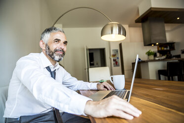 Portrait of smiling businessman working at his home office - MBEF001150