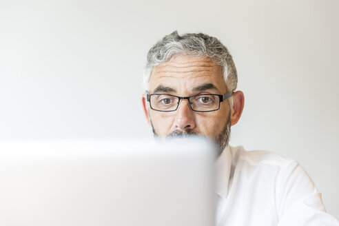 Portrait of astonished businessman working at laptop - MBEF001164