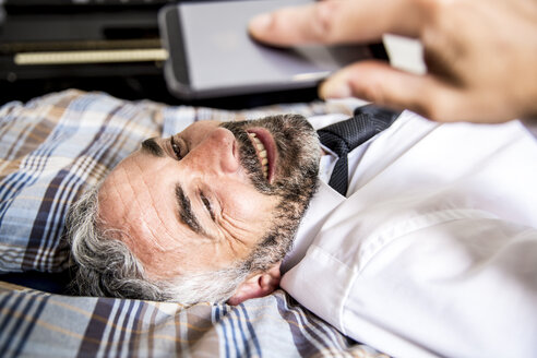 Portrait of smiling businessman lying on his bed looking at his smartphone - MBEF001225