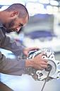 Car mechanic working on gearbox in repair garage - ZEF000531
