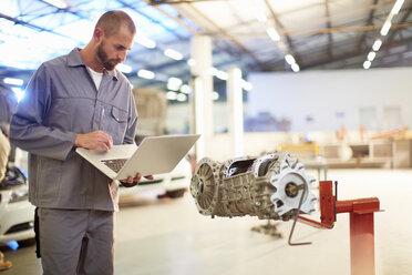 Car mechanic using laptop in repair garage - ZEF000634